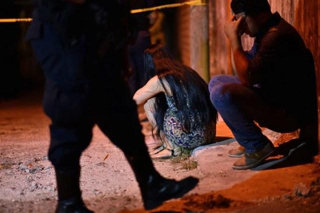 Familiares y amigos se lamentan frente al lugar donde murieron 13 personas en un tiroteo en Minatitlán. (ANGEL HERNANDEZ / AFP)