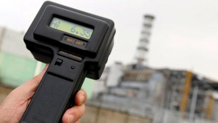 Un visitante mide la radiación frente a la central nuclear de Chernobyl, en Ucrania, el pasado 31 de marzo. EFE/Sergey Dolzhenko