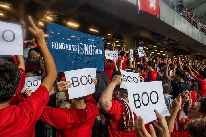 Hinchas del equipo de fútbol de Hong Kong dan la espalda al campo durante la entonación del himno chino. / Lam Yik Fei / The New York Times