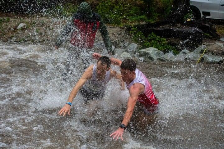 Dos competidores del Mundial de Montaña, cruzando un arroyo en Villa La Angostura.  Foto: Prensa K42