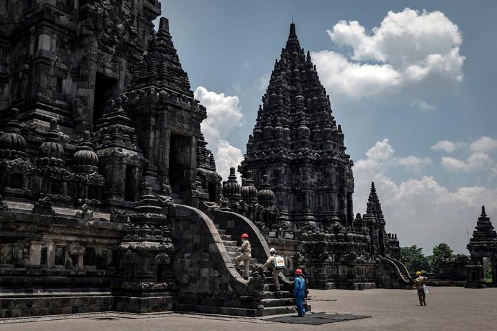Algunos trabajadores desinfectan el complejo de templos Prambanan, que permanece cerrado al público, en Yogyakarta, Indonesia, el martes 17 de marzo de 2020. (Ulet Ifansasti/The New York Times)