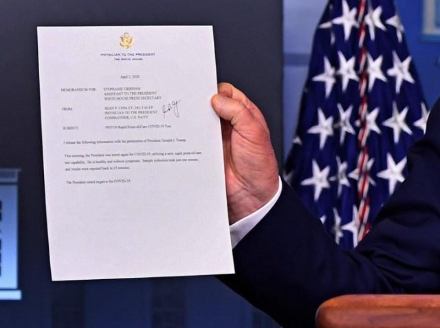 El presidente de los Estados Unidos, Donald J. Trump, sostiene un memorándum en el que dice que dio negativo de coronavirus. /EFE / EPA / KEVIN DIETSCH/