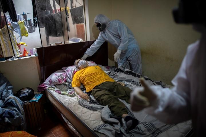 Venezolanos retiran el cuerpo de otra persona muerta por coronavirus. / AP