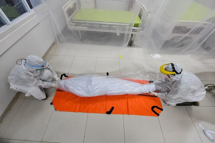 Empleados de una morgue trabajan con el cadáver de un muerto por Covid-19. Foto AFP.