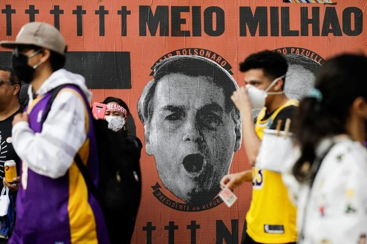 """A mural in San Pablo, with the face of Jair Bolsonaro and the inscription """"Half a million"""", in reference to the number of deaths from coronavirus in Brazil, Photo: AP"""