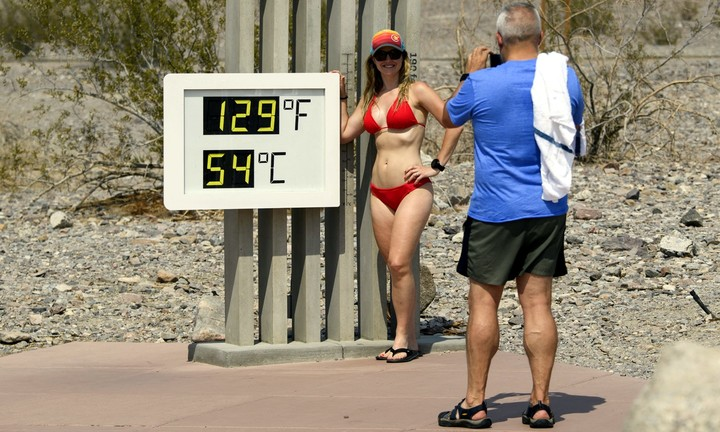 A couple take a photo next to a sign that reads 54 degrees Celsius in Death Valley National Park in Furnace Creek, California, United States.  Photo: AFP