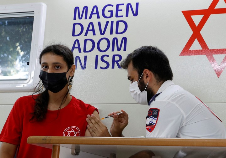 A teenage girl receives the Pfizer vaccine in Israel.  AFP photo