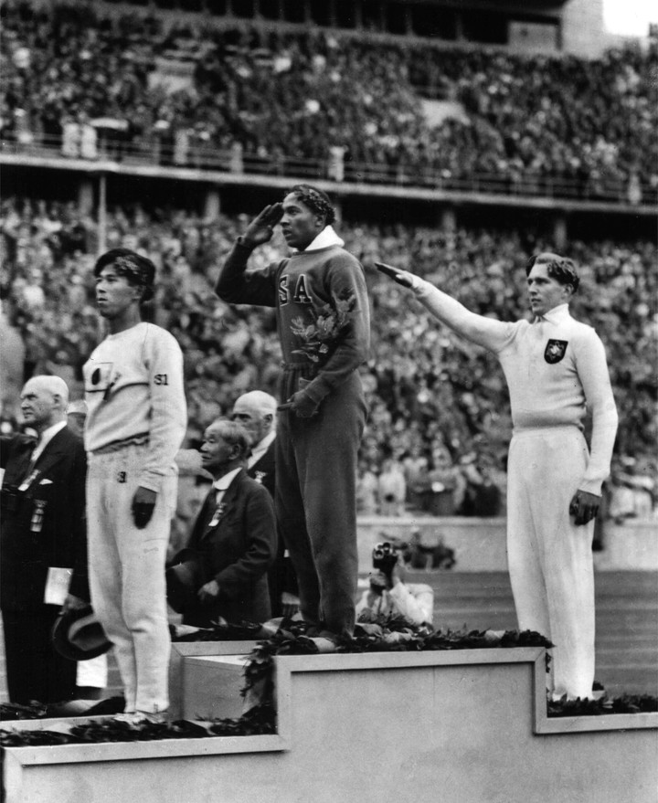 Jesse Owens on the podium of the 1936 Berlin long jump. To his left, the German Lutz Long gives the Nazi salute.  (AP)