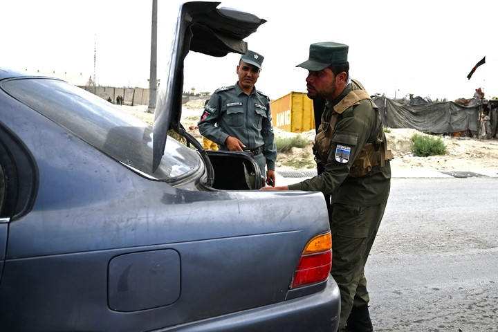 Afghan policemen search the trunk of a car during an operation on the entrance route to Kabul.  Photo: AFP