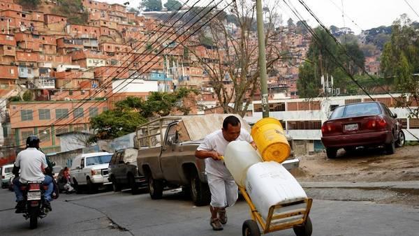 """Un hombre empuja una carretilla cargada de contenedores de agua en un barrio llamado """"El Tanque"""" en Petare en Caracas. (REUTERS)"""