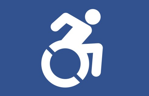 Redesign of the traditional logo, white stick figure and wheels, blue background. The new one is more dynamic, with the wheelchair user angled forward to suggest motion. The wheels have slits in them to also suggest fast forward rotation. The hands and arms are back behind the body about to use the push rims.