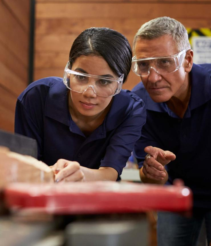 A female international student wearing safety goggles works at a carpentry table while her professor wearing safety goggles watches over her shoulder