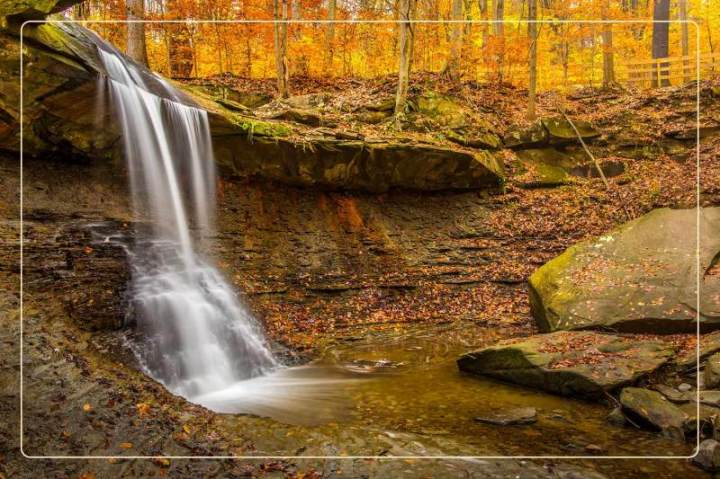a waterfall among fall foliage at Cuyahoga Valley National Park, a dog-friendly national park where one can go hiking with dogs