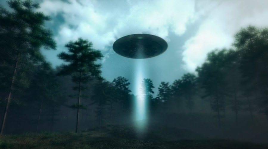 UFO with a blue beam flies in a forrest