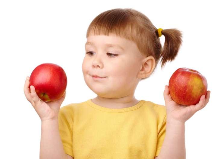 Un niño sosteniendo dos manzanas y eligiendo entre ellas, de manera similar a la forma en que los algoritmos usan condicionales para elegir.