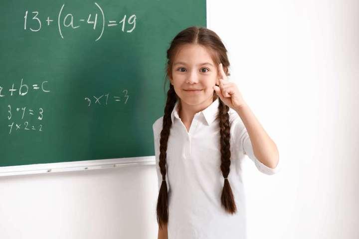 Un niño de pie frente a una pizarra con variables algebraicas escritas en él