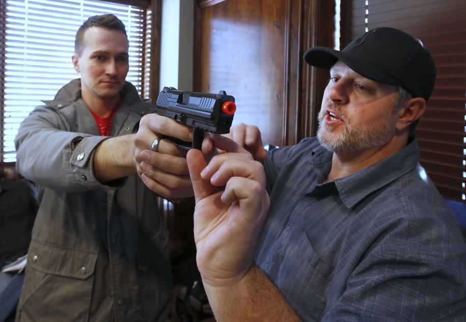 """PROVO, UT - DECEMBER 19: Damon Thueson, (R) shows Joel Zae, (L) how to hold a gun at a gun concealed carry permit class put on by """"USA Firearms Training"""" on December 19, 2015 in Provo, Utah. Demand for concealed carry permits have spiked in the last several weeks with the terrorists attacks in Paris and the United States. (Photo by George Frey/Getty Images)"""