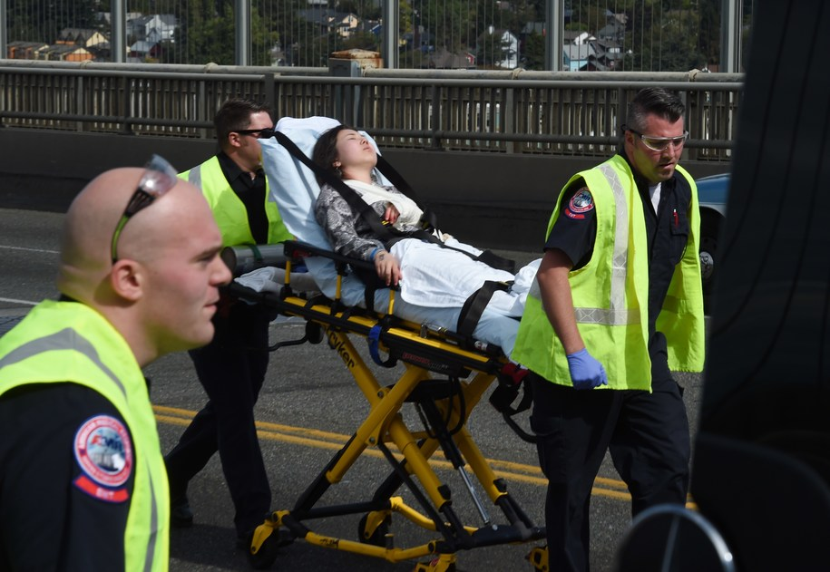 An injured person is taken to an ambulance at the scene of a crash between a tour bus and a tourist duck boat on the Aurora Bridge in Seattle, Washington on September 24, 2015. At least four people were killed and several were critically injured when a bus collided with a tour vehicle on a bridge in the US West Coast city of Seattle, officials said. AFP PHOTO/ MARK RALSTON        (Photo credit should read MARK RALSTON/AFP/Getty Images)