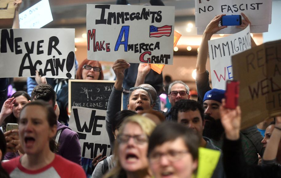 Protesters shout and hold up signs at San Francisco International Airport in San Francisco, California on January 29, 2017..US President Donald Trump issued an executive order yesterday barring citizens of seven Muslim-majority countries from entering the United States for the next 90 days and suspends the admission of all refugees for 120 days. / AFP / Josh Edelson        (Photo credit should read JOSH EDELSON/AFP/Getty Images)