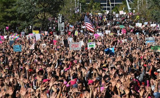 "Protesters, part of a 500,000 strong crowd, attend the Women's Rally on the one-year anniversary of the first Women's March in Los Angeles, California on January 20, 2018..Protestors took to the streets en masse across the United States Saturday, hoisting anti-Donald Trump placards, banging drums and donning pink hats for a second Women's March opposing the president -- one year to the day of his inauguration. Hundreds of thousands of marchers  assembled in Washington, New York, Chicago, Denver, Boston, Los Angeles and other cities nationwide, many donning the famous pink knit ""pussy hats"" -- a reference to Trump's videotaped boasts of his license to grope women without repercussions.. / AFP PHOTO / Mark RALSTON        (Photo credit should read MARK RALSTON/AFP/Getty Images)"