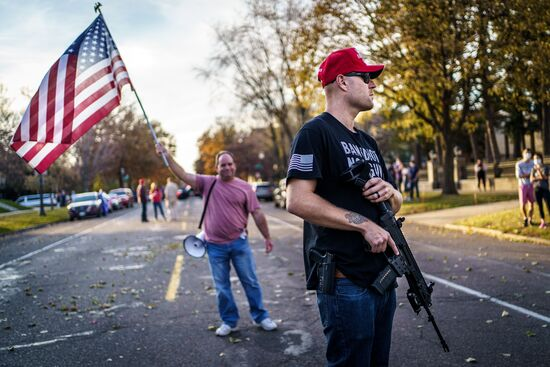 "A supporter of US President Donald Trump keeps a hand on his gun during a ""Stop the Steal rally"" in front of the residence of Minnesota Governor Tim Walz in St Paul, Minnesota, on November 7, 2020. - Democrat Joe Biden has won the White House, US media said November 7, defeating Donald Trump and ending a presidency that convulsed American politics, shocked the world and left the United States more divided than at any time in decades. (Photo by Kerem Yucel / AFP) (Photo by KEREM YUCEL/AFP via Getty Images)"