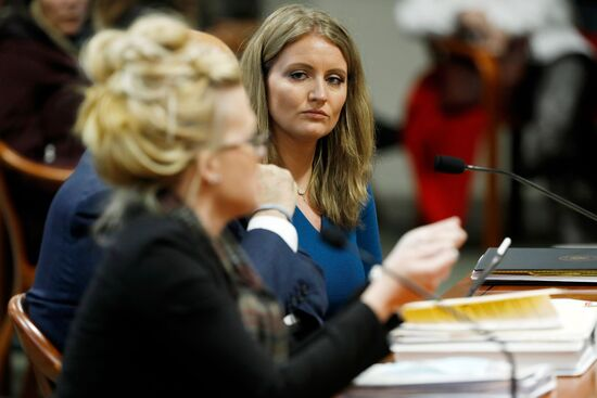Lawyer Jenna Ellis (R) listens to Melissa Carone, who was working for Dominion Voting Services, as she speaks in front of the Michigan House Oversight Committee in Lansing, Michigan on December 2, 2020. - Jenna Ellis, one of US President Donald Trumps lawyers, has tested positive for coronavirus, according to media reports on December 8, 2020. Ellis had attended a Christmas party at the White House. Her reported positive test also comes just days after Trump lawyer Rudy Giuliani tested positive. He was hospitalized on December 6, 2020. (Photo by JEFF KOWALSKY / AFP) (Photo by JEFF KOWALSKY/AFP via Getty Images)