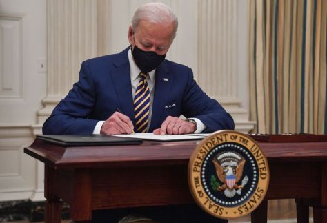 US President Joe Biden signs executive orders for economic relief to Covid-hit families and businesses in the State Dining Room of the White House in Washington, DC, on January 22, 2021. (Photo by Nicholas Kamm / AFP) (Photo by NICHOLAS KAMM/AFP via Getty Images)