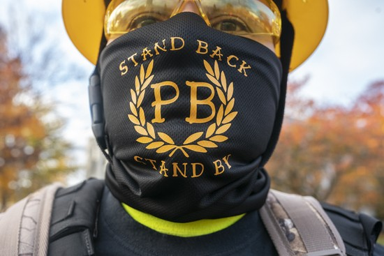 "SALEM, OR - NOVEMBER 07: A Proud Boy displays a bandana with the phrase Stand Back, Stand By, a reference to President Trumps statements about the group  during a ""Stop the Steal"" rally on November 7, 2020 in Salem, Oregon. Angry supporters of President Trump took to the streets across the country following reporting that President-elect Joe Biden had won the election. (Photo by Nathan Howard/Getty Images)"