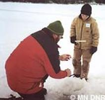 volunteer helping a child ice fish