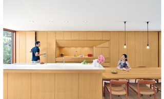 "Kitchen, Wood Cabinet, and Pendant Lighting For a Toronto couple with a love of minimalist Japanese architecture, a sleek, storage-packed kitchen was the first priority in their home's renovation. In the kitchen, white oak used for the cabinets, kitchen island, and dining table is finished with double-boiled linseed oil, which can be reapplied by the homeowners as the wood mellows and patinas. The custom beveled edge for the island's ""Blizzard"" white Caesarstone countertop forgoes the standard one-inch countertop overhang to save on space and maintain a sleek feel. A Vola faucet is used with a sink by Mekal."
