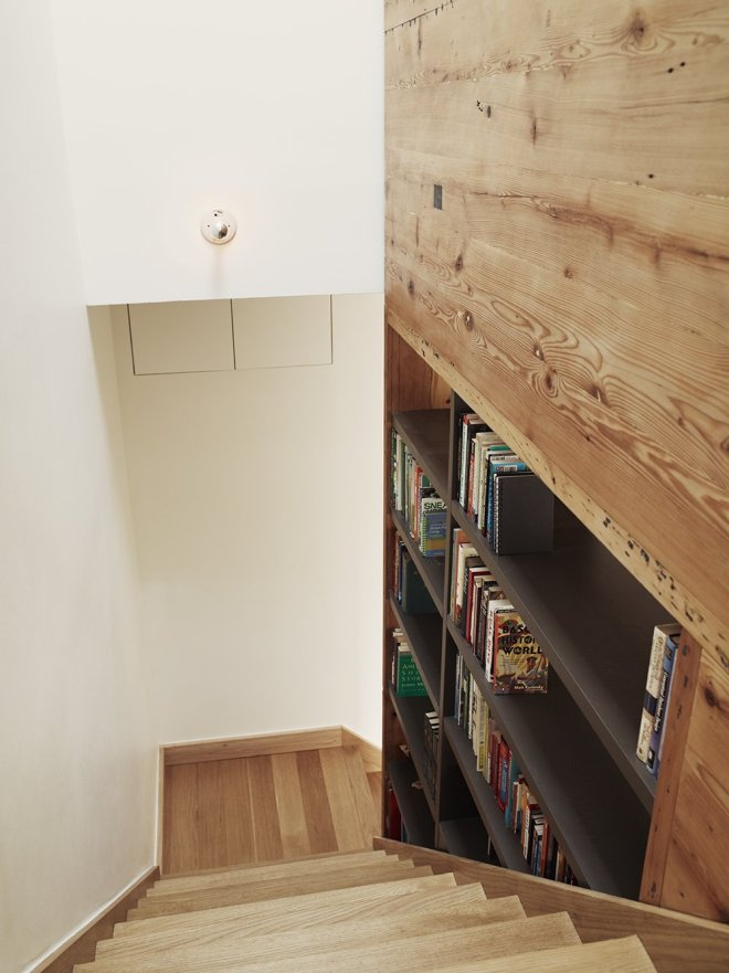 6 Hallway Hacks to Turn Them Into Usable Space - Photo 8 of 12 - Creating a library along a staircase out of open shelving means that the books can be accessed from both the staircase and the stair hall on the other side.