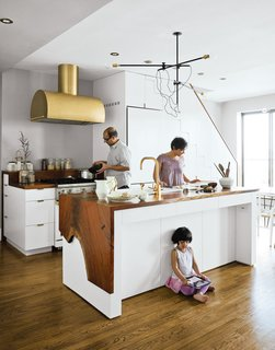 Kitchen, Wood Counter, Medium Hardwood Floor, White Cabinet, Range Hood, Range, Vessel Sink, Pendant Lighting, and Recessed Lighting A couple takes a minimalist approach to their Brooklyn apartment, focusing on supple materials, subtle gradations of color, and custom finishes by local craftsmen. The Mandayam–Vohra family gathers under one of Workstead's signature three-arm chandeliers, shown here in its horizontal configuration. Bartenschlager designed the white cabinets and is responsible for the walnut counters both on the kitchen island and near the stove.