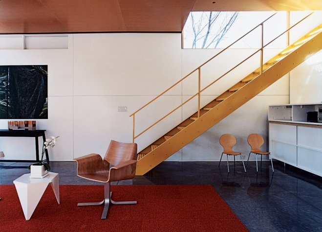 10 Smart and Surprising Under-Stair Design Solutions - Photo 5 of 10 - In this home by architect Charlie Lazor in Minneapolis, the space under this open-riser metal stair has been allocated as overflow storage and seating for the living room. Although it may initially seem like an unusable area, the height of the stair means that the space is in fact usable by someone seated or reaching for items in the storage cabinet along the back wall. By carefully placing the chairs, the space appears useful but not cluttered.