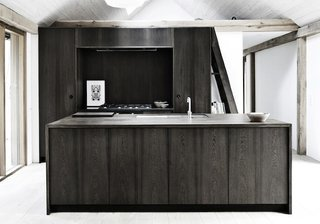 Tucked away in the woods of Denmark, furniture design company Kobenhavens Mobelsnedkeri designed this vacation retreat that boats a striking pitch-black kitchen island. The home features a restrained color palette complemented with natural touches; the floor is a delicate pale oak, which contrasts with the bold statement of the dark cabinets and island.