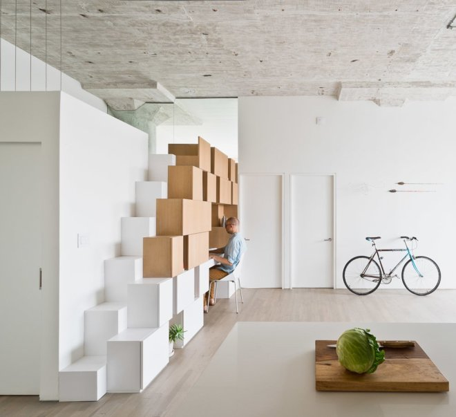 10 Smart and Surprising Under-Stair Design Solutions - Photo 7 of 10 - In the family room of this former industrial loft in Brooklyn that was renovated by SABO project, a new staircase leads to a mezzanine level. The alternating tread steps double as cabinets that are free of knobs and visible hardware, creating a graphic statement piece in the room. The cabinets give way to a workspace that's complete with open and closed shelving so that the space can remain uncluttered.