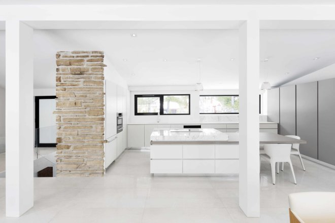 These 30 White Kitchens Are Anything But Ordinary - Photo 9 of 30 - The interior features neutral colors and streamlined appliances like the Miele oven, stovetop, and refrigerator, along with the Espace Cuisine cabinets.