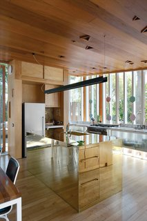 In Auckland, New Zealand, architect Michael O'Sullivan and his partner Melissa Schollum braved a miniscule budget, withering looks from friends, and nasty nail-gun injuries to design and build their perfectly proportioned family home. The reflectivity of the brass kitchen island makes it seem to dematerialize.