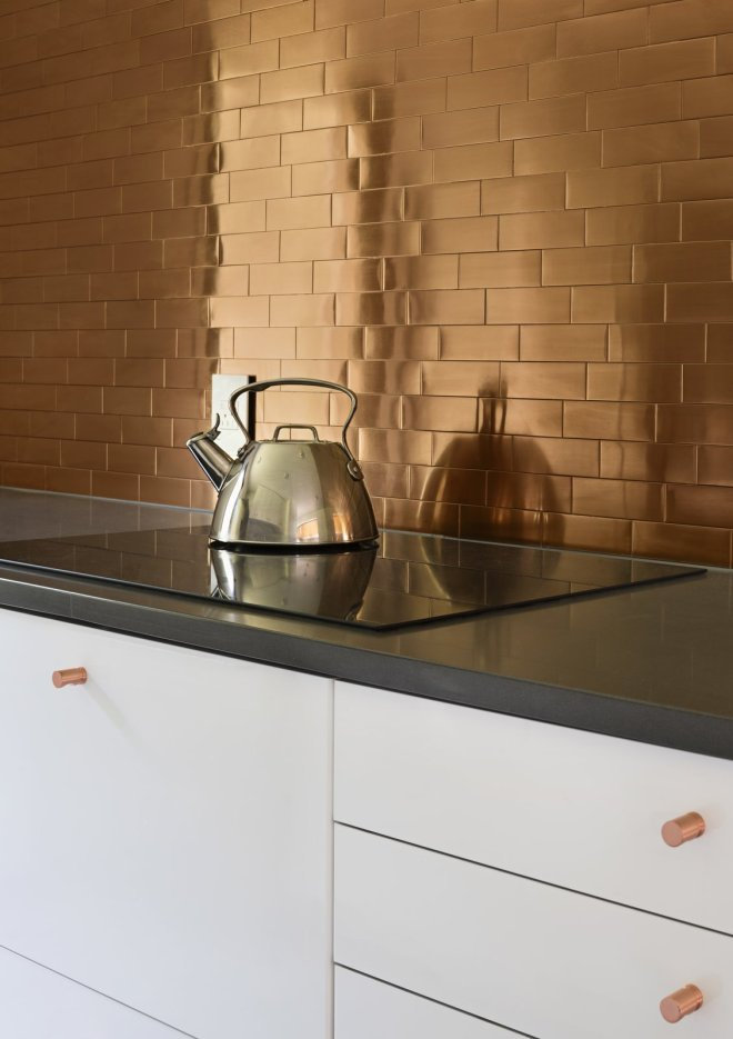 25 Backsplash Ideas For Your Kitchen Renovation - Photo 1 of 25 - In the kitchen, copper-colored stainless steel tiles from TileBar create a glowing backsplash. The cabinetry is by IKEA, the countertop is Caesarstone, and the induction cooktop is by Bosch.