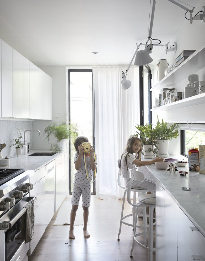 These 30 White Kitchens Are Anything But Ordinary - Photo 14 of 30 - The narrowness of the house required the design to make effective yet frugal uses of space. Precise positioning of walls, doors, and windows were crucial as each floor was planned to serve a purpose. The first floor is a continuous public space with a living room, dining area, kitchen, and library opening to gardens in the front and back.