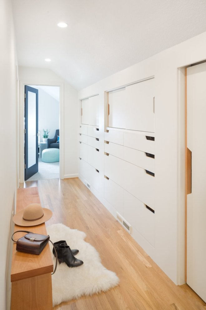 6 Hallway Hacks to Turn Them Into Usable Space - Photo 2 of 12 - Custom millwork and cabinetry can be a great way to add storage while keeping the hallway looking clean, neat, and bright. Cut-outs in the doors instead of knobs or cabinet handles ensure that hardware doesn't take up any extra space in the narrow corridor.
