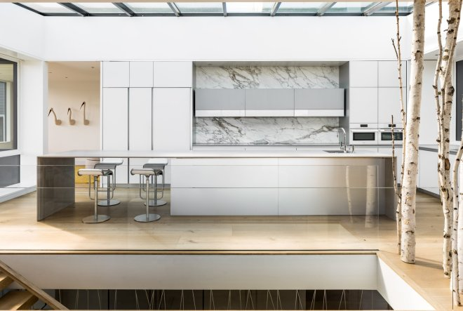 These 30 White Kitchens Are Anything But Ordinary - Photo 3 of 30 - An expansive skylight extends the full width and length of the kitchen, flooding natural light into the core of the open and connected living spaces.