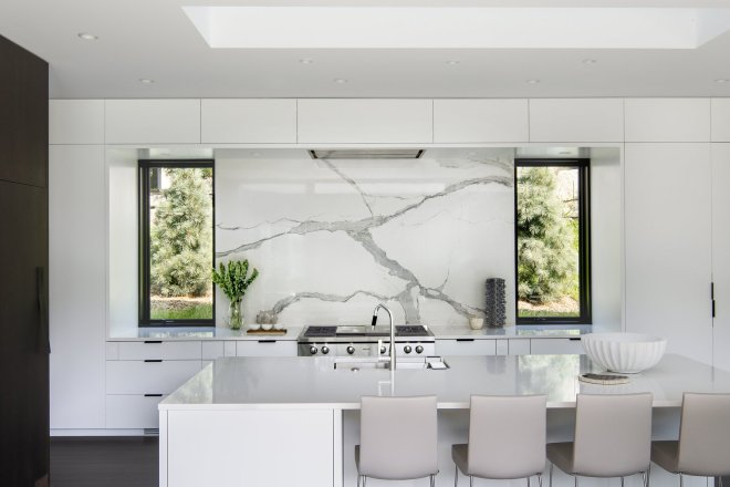 These 30 White Kitchens Are Anything But Ordinary - Photo 7 of 30 - Built on a hilly, South-facing site populated with mature heritage trees in an established neighborhood, this home finds its sophisticated form through the traditional motifs. The highly linear, open floor plan is adorned with chic finishes, including a sleek wall of custom cabinetry.