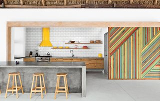 Kitchen, Concrete Counter, Wood Cabinet, Range Hood, and Range By eliminating walls and incorporating a series of interior gardens, architect José Roberto Paredes creates an eclectic and inspired El Salvador beach house. In the kitchen, rough-hewn materials like a eucalyptus-log-and-thatch roof offset the monolithic concrete island and glossy subway tile backsplash. Claudia & Harry Washington built the vivid wooden sliding walls, which are inspired by the palm leaves that change color and create diagonal patterns in trees near the house. The bar stools were a street market discovery.