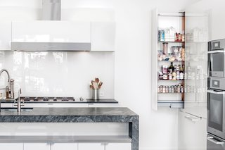 """Kitchen, White Cabinet, Range Hood, Wall Oven, and Cooktops Painters accomplished the high-gloss finish on the cabinets of a kitchen in San Francisco by applying a coat of paint, polishing it with very high-grit sandpaper, repeating the process for each layer, then topping it with three coats of clear varnish. """"It's like an auto body,"""" says builder Jeff King. """"It's incredibly beautiful."""" The island provides shelving space and storage as well as a second sink, an is topped with pietra grigio marble."""