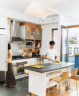 Kitchen, Granite Counter, White Cabinet, Range, and Range Hood Avid cooks, Jinhee and John spend part of every day around their custom-built kitchen island, surrounded by Compasso d'Oro barstools. The island is on castors, so it easily moves around the kitchen as needed. An edamame plant on their patio occasionally provides leaves for Korean dishes.