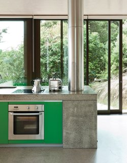 Kitchen, Concrete Counter, Cooktops, and Wall Oven At a seaside New Zealand house, the simple kitchen has strandboard cabinetry and an MDF island that conceals a fireplace at one end. The bright green cabinetry of the island are a happy pop of color that references the native greenery outside.