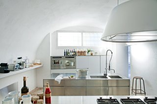 "Kitchen, Metal Counter, Metal Cabinet, Drop In Sink, Range Hood, Wall Oven, Open Cabinet, Table Lighting, and Range The acclaimed Italian designers Ludovica+Roberto Palomba carved a serene retreat out of a 17th-century oil mill in Salento, Italy, filling it with custom creations and their greatest hits. In their minimalist kitchen: sleek steel cabinet systems and the Kono range hood from Elmar. The multi-functional stainless steel island measures 20"" deep and was designed by the couple for Elmar."
