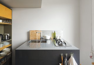 Kitchen, Engineered Quartz Counter, Cooktops, and Undermount Sink With clever storage and a retractable skylight, a London apartment designed by metalworker and owner Simone ten Hompel and Roger Hynam of Rogeroger Design Solutions feels larger than its 576 square feet. The team worked in a uniquely collaborative way, with Ullmayer Sylvester planning the space, Hynam creating the built-in storage and the kitchen island, and ten Hompel making models and scrawling on the wall to better envision their proposals. The kitchen island features a compact cooktop by Whirlpool and an integrated drainboard incised into the countertop for easy cleaning.