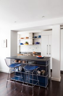 Kitchen, Stone Counter, White Cabinet, and Dark Hardwood For a 1,500-square-foot condo in the Meatpacking District, Reddymade Design reconfigured the space to merge the kitchen, dining room, and living room into an open-plan arrangement. In the kitchen, the island unit is a modular piece by USM with a Vermont Black slate countertop. The Harry Bertoia stools are from Design Within Reach. The backsplash features Delft tiles, and the stove and range is Bertazzoni.