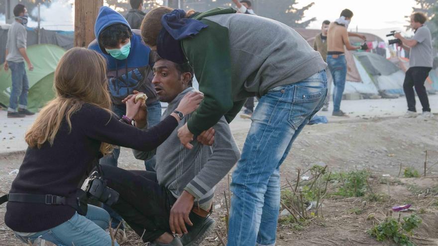 Varios voluntarios atienden a un afectado por los gases lacrimógenos en el campo de Idomeni | FOTO: Pablo Gabande